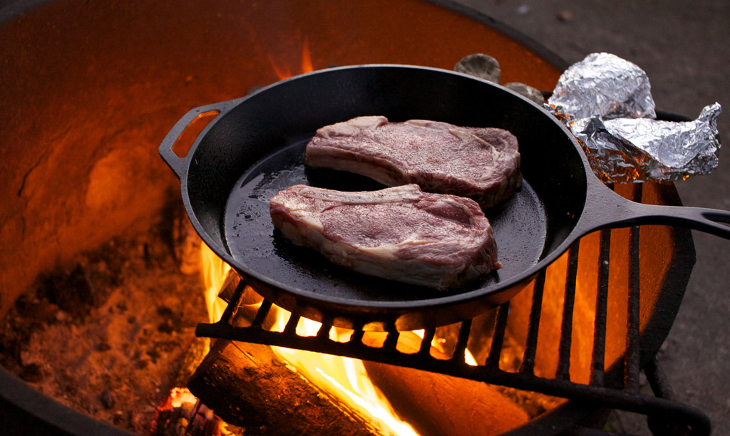 Cooking steaks over an oven campfire
